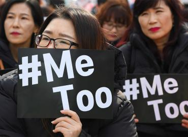"Two women holding banners that say ""#MeToo"""