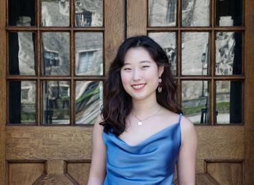Gina Kwon in front of a door at Trinity College