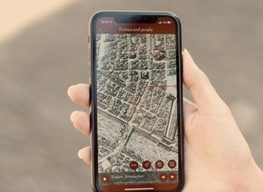 A hand holding a phone with the screen showing a map.