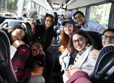 A group of students posing for a picture on a bus.