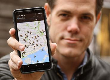 Jon Johnson holing up a phone showing a map.