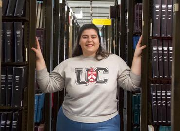 Kaitlyn Ferreira standing between two bookshelves in a library