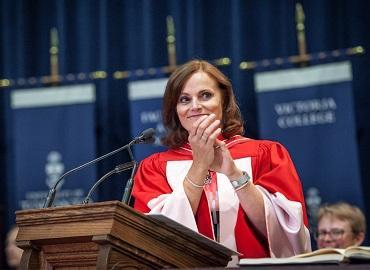 Judy Goldring clapping behind a podium at Convocation 2019