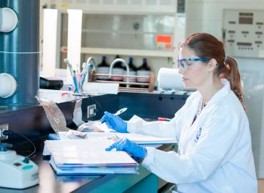 A woman, wearing a lab coat and safety glasses, writes in her notebook inside a lab.