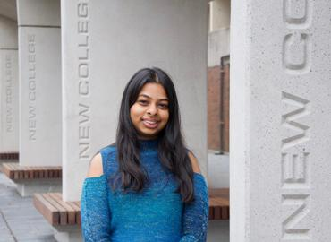 Shweta Mogalappi in front of the New College concrete sign