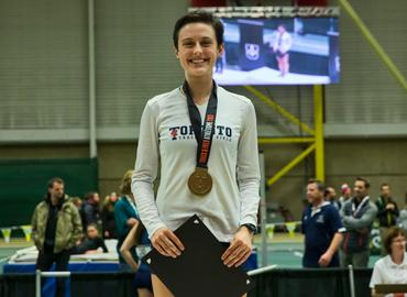 Gabriela DeBues-Stafford, standing proudly with a medal around her neck.