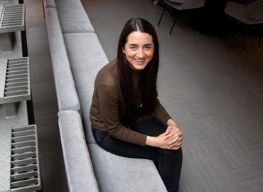 Tara Suri sitting on a grey bench