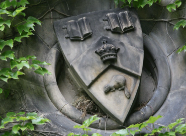 UofT crest on a building made of stone.