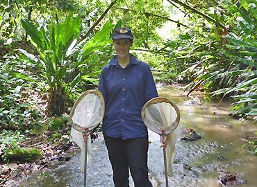 Alex De Serrano holding two fishing nets in a stream.