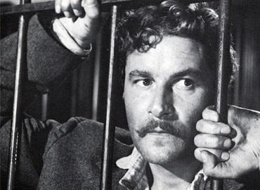 Black and white photo of man in prison looking forlorn, his hands on the bars