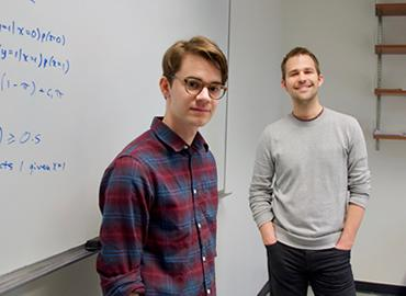 Ashton Anderson and undergraduate student Isaac Waller standing in front of equations