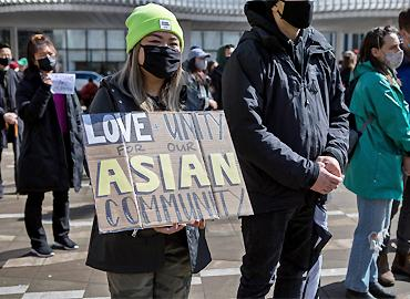 A women holding a sign that says - Love, unity for Asian community.