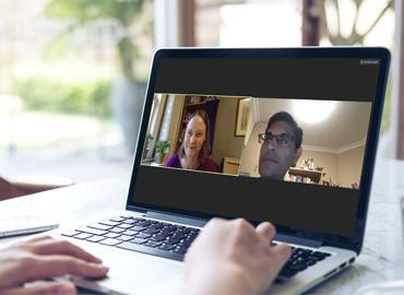 Jennifer Wells and Rajeev Chib are seen in split screen on a video call on a laptop.