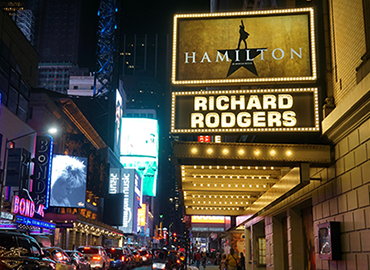 Image of a theatre on Broadway with ad for Hamilton