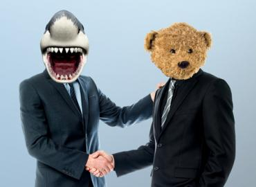 Two businessmen shaking hands one with a superimposed shark head and the other with a teddy bear head.
