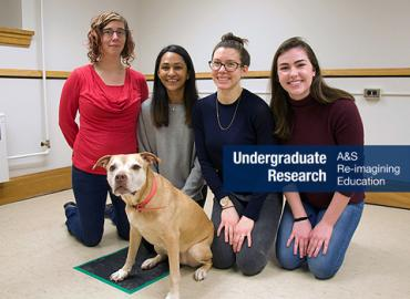 Three students with their professor and Pumpkin the golden retriever