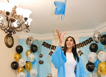 Dildeep Kullar, dressed in a sky blue gown, throws a matching mortarboard into the air in her home