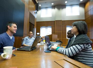 A professor has a discussion with a group of graduate students inside a meeting room.