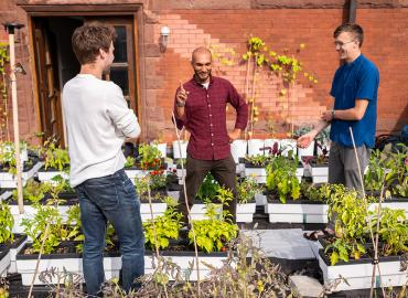 Nicolas Côté, Rashad Brugmann and Nathan Postma in Trinity College's rooftop garden on the St. George campus