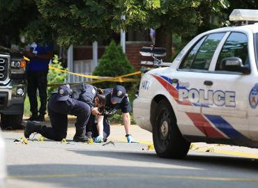 Two police officers photograph evidence at a crime scene next to a Toronto police car