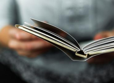 Close up on hands holding a book