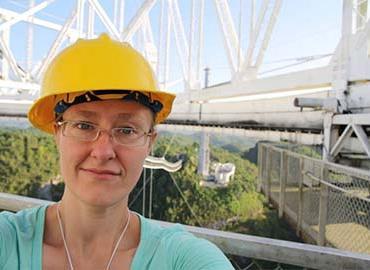 Jennifer West in a hardhat on a steel structure