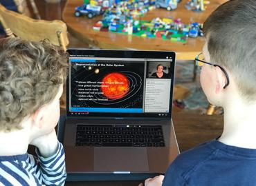 Two children looking at the Astro at Home program on a laptop