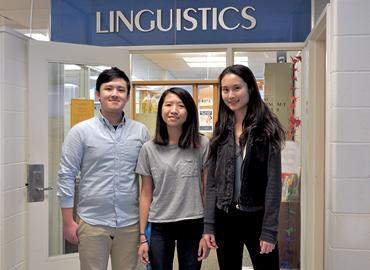 Three students stand in-front of the Linguistics office.