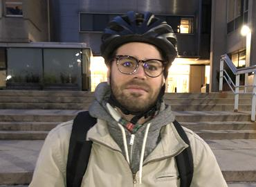 Mischa Young poses wearing a bike helmet.