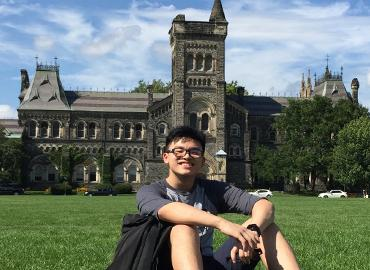 Martin Mak sitting in front of Kings College Circle on a sunny day.