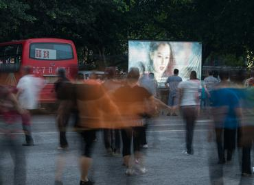 A woman's face on a screen in a Chinese city