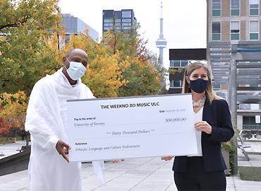 Bikila Award president Tessema Mulugeta presents A&S dean Melanie Woodin standing outside with masks on holding a large cheque.