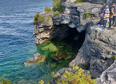 A cliff with a body of water below.