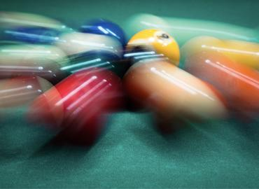 Pool balls rolling quickly across a table.