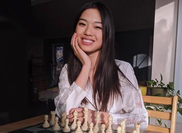 Qiyu Zhou in front of a chess board