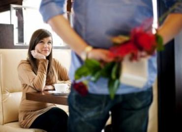 Woman sitting at table, man approaching her with flowers behind his back