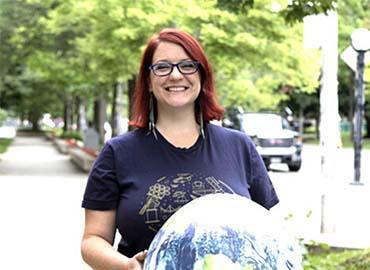 Renée Hložek holding a model universe globe outdoors