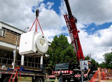 Siemens Prisma 3 Tesla MRI being lifted by a crane outside the Centre for Biological Timing and Cognition.