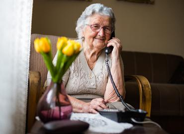 An elderly person on the phone smiling.