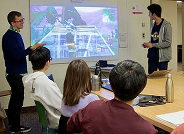 Assistant Professor Felan Parker shows off a new video game in front of an engaged class.