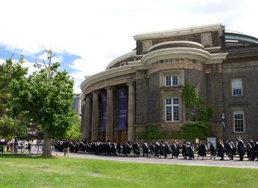 A group of new graduates walk into convocation hall on a sunny June day.
